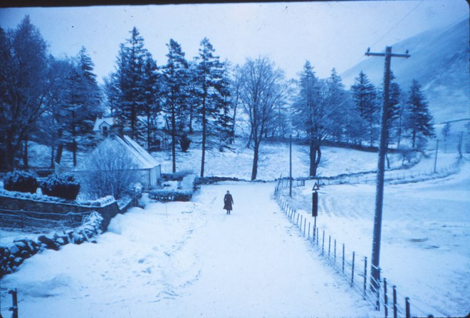 Someone walks up the road in winter close to Glenshee Church.