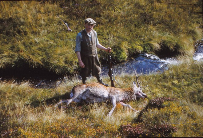 A man on a shoot stands over his prize.