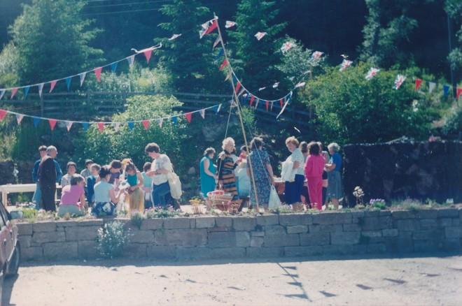 A group of people gathered under bunting outside the Inn.