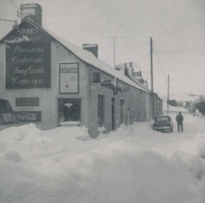 Main Street Kirkmichael in the snow. Jock MIlne by the car. 16/02/1963
